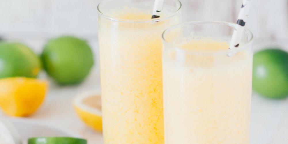 two glasses of lemonade with straws and lemons and limes