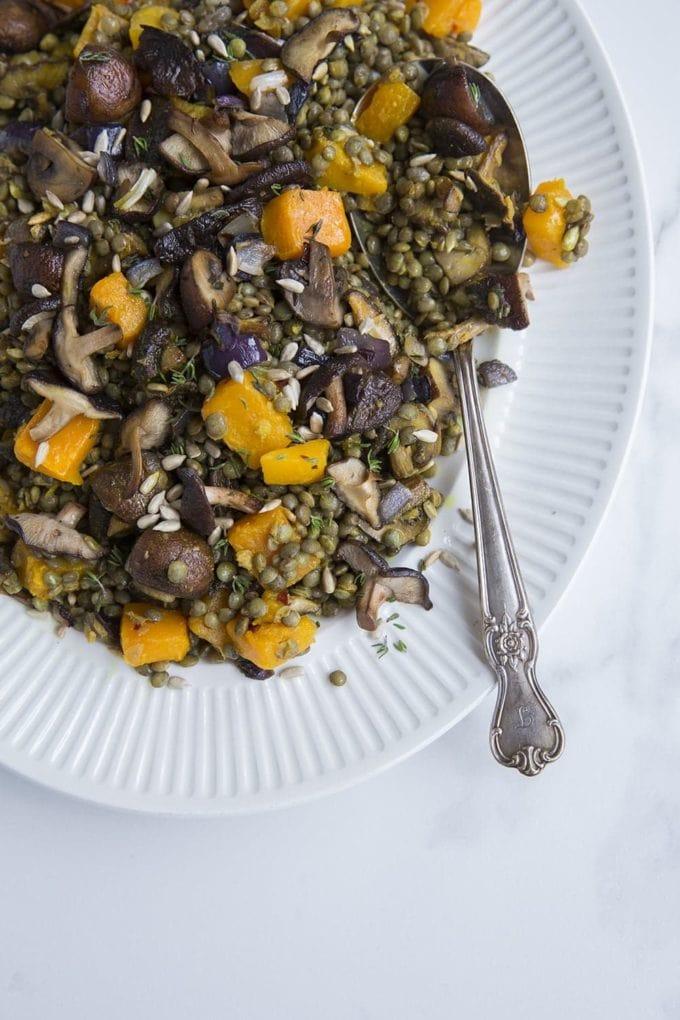 lentil, squash and mushroom salad on platter with serving spoon
