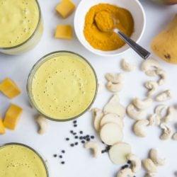 turmeric smoothies in glass with turmeric, mango, cashew