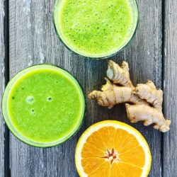 green smoothies with sliced orange and ginger on wood table