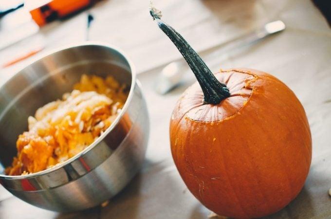 pumpkin with bowl of pumpkin seeds