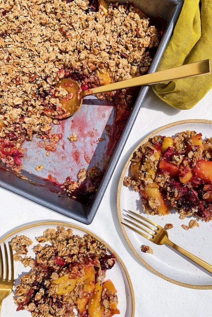 vegan peach blackberry crumble on white plates