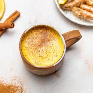 mug of apple cider with cinnamon sticks, ginger and lemon
