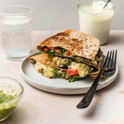 spinach quesadilla on a plate with black fork, jar of pesto and cashew cream