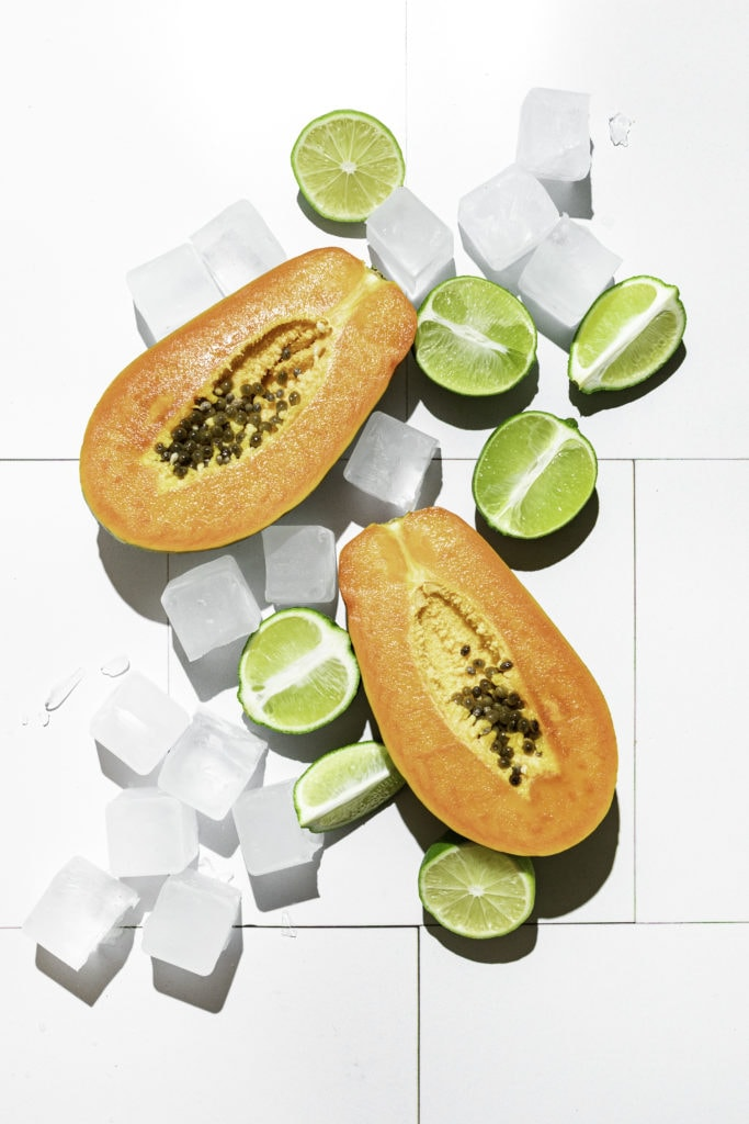 papayas and limes with ice cubes