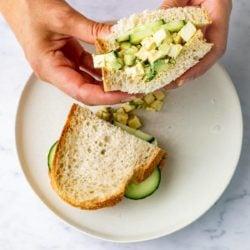 hands holding vegan egg salad sandwich on white plate